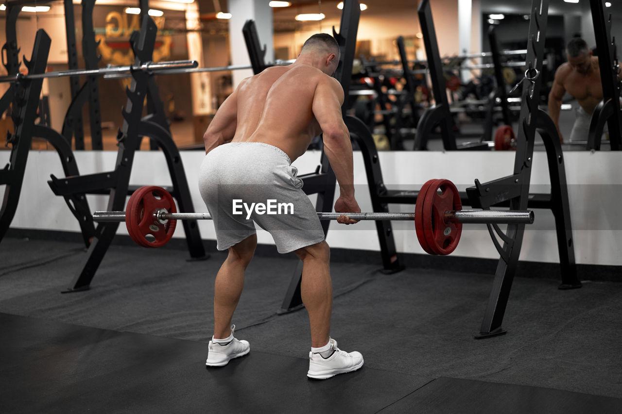 Rear view of shirtless man exercising at gym