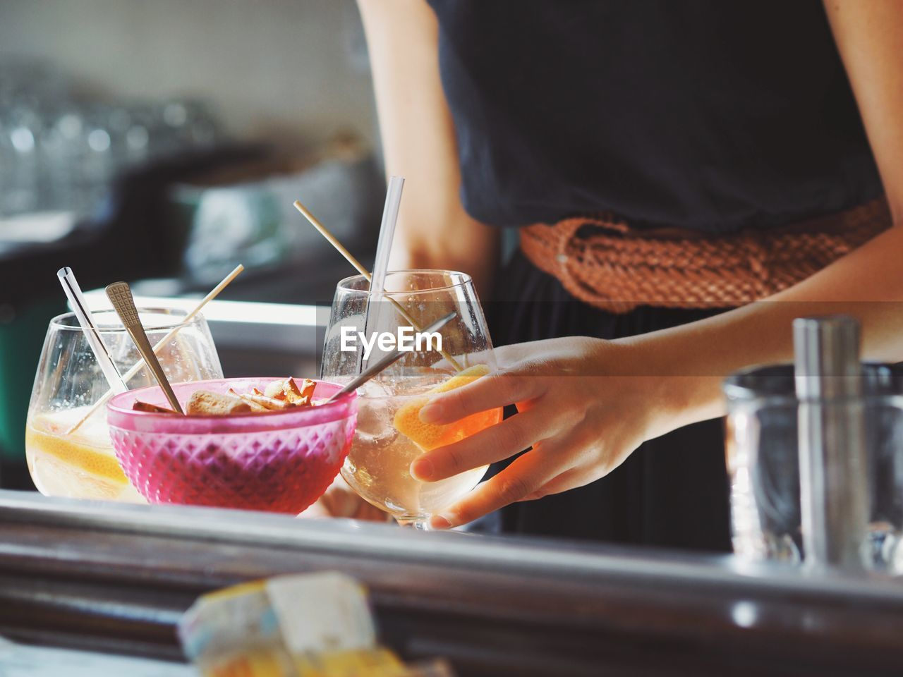 Midsection Of Waitress Serving Food And Drinks On Restaurant Table