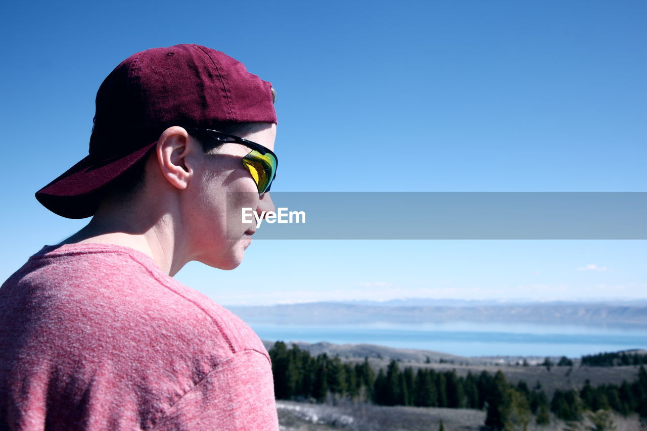 Close-up of young man wearing sunglasses while looking at view