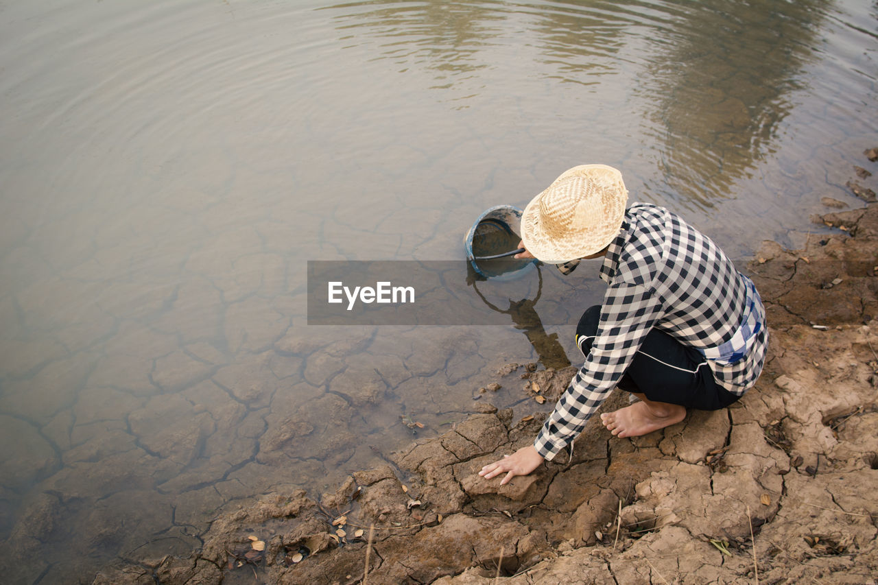 High Angle View Of Person Crouching Over Cracked Field While Filling Water From Lake In Bucket
