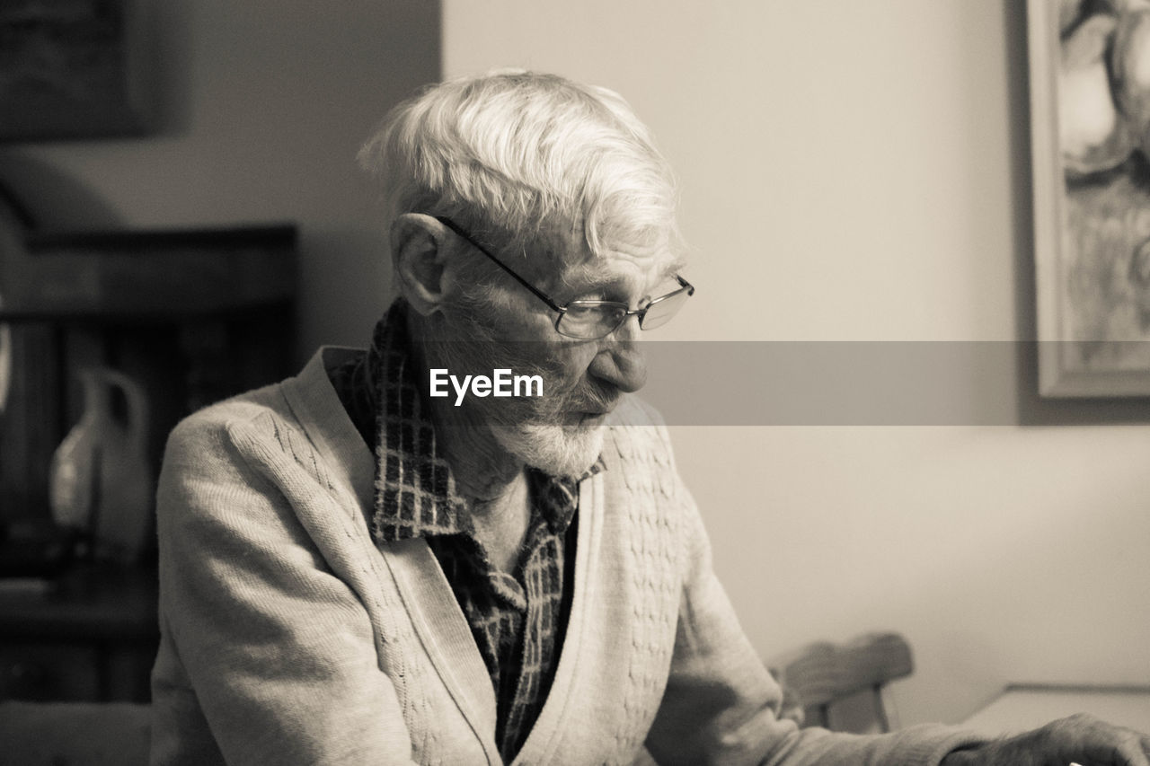 Senior Man Wearing Eyeglasses Sitting At Home