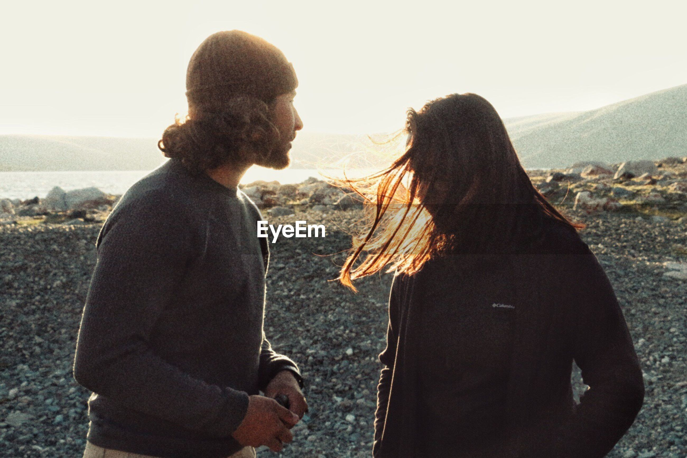 two people, real people, togetherness, rear view, love, women, bonding, leisure activity, young women, standing, men, lifestyles, day, mountain, couple - relationship, water, young adult, sunset, outdoors, nature, beauty in nature, friendship, sky, adult, people