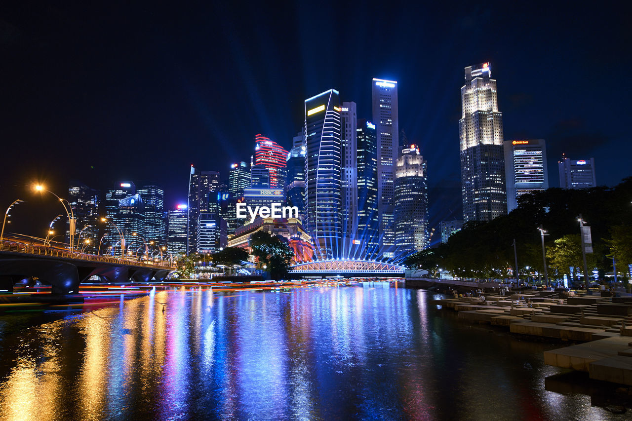 night, architecture, built structure, illuminated, water, building exterior, city, river, bridge, bridge - man made structure, connection, building, sky, waterfront, reflection, cityscape, office building exterior, transportation, skyscraper, no people, tall - high, modern, outdoors, nightlife, financial district