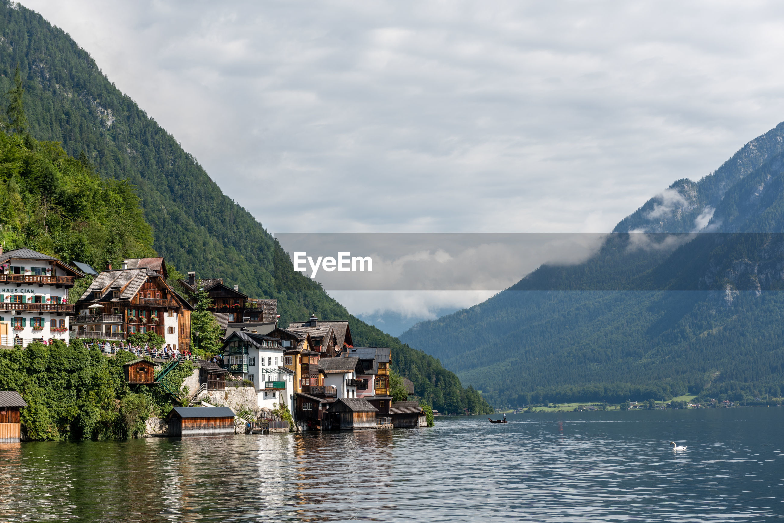 HOUSES BY LAKE AGAINST MOUNTAINS