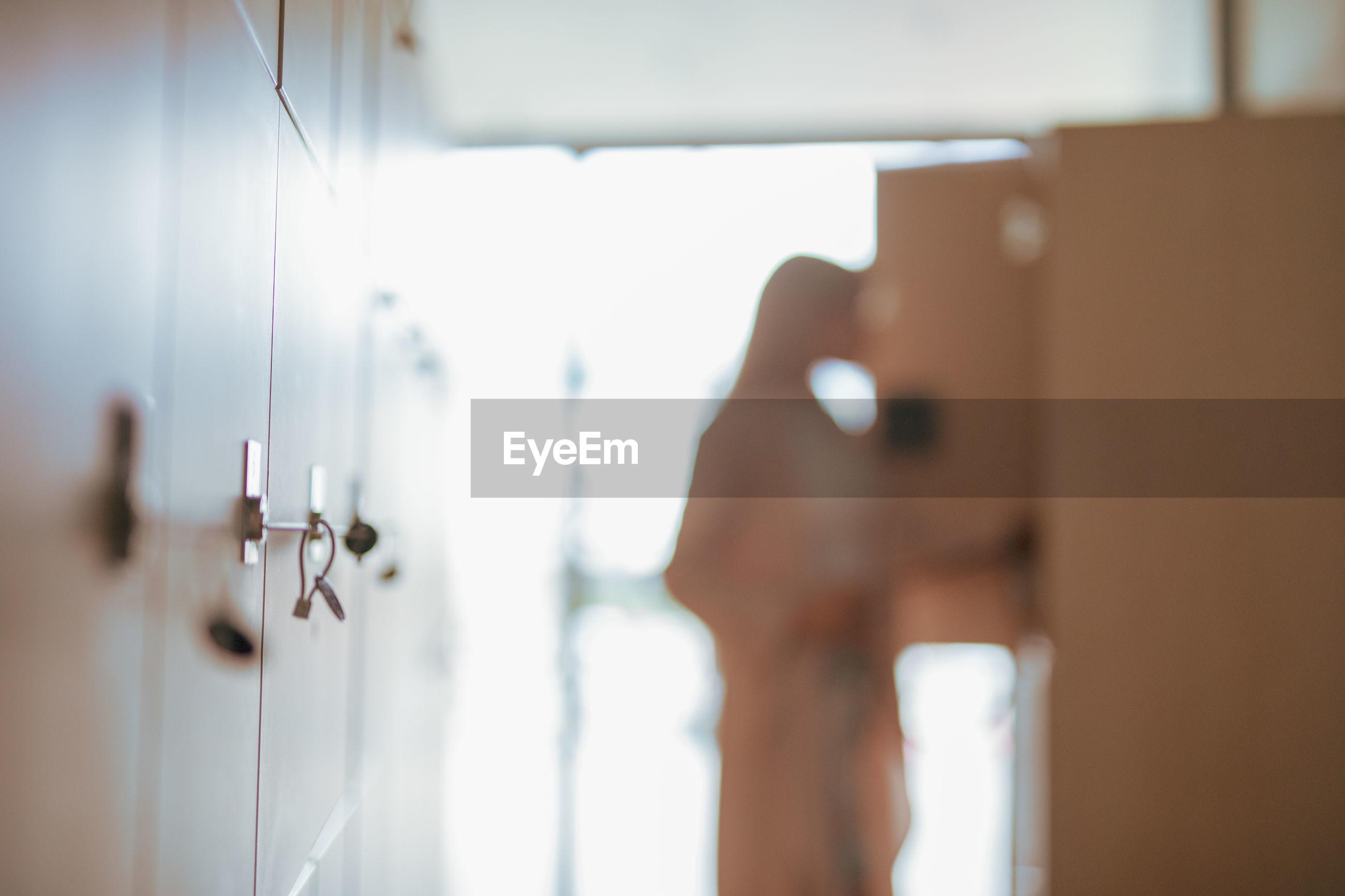 Woman standing by door in corridor