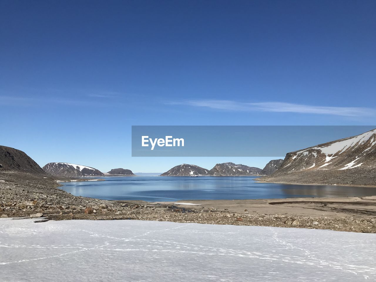 Scenic View Of Sea By Mountains Against Blue Sky