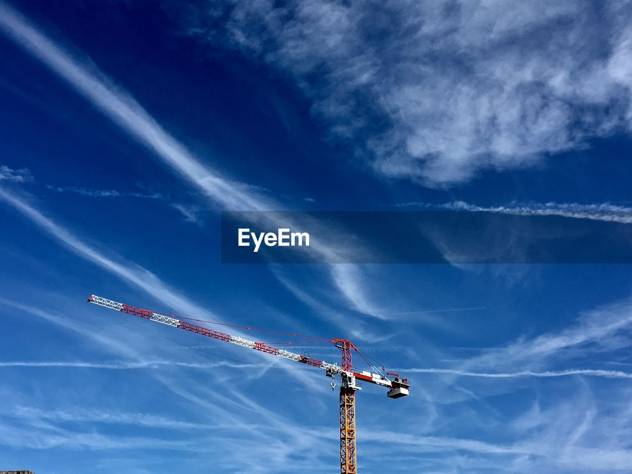 cloud - sky, sky, construction industry, low angle view, blue, crane - construction machinery, nature, no people, day, construction site, machinery, industry, development, construction equipment, outdoors, metal, vapor trail, crane, construction machinery, building - activity