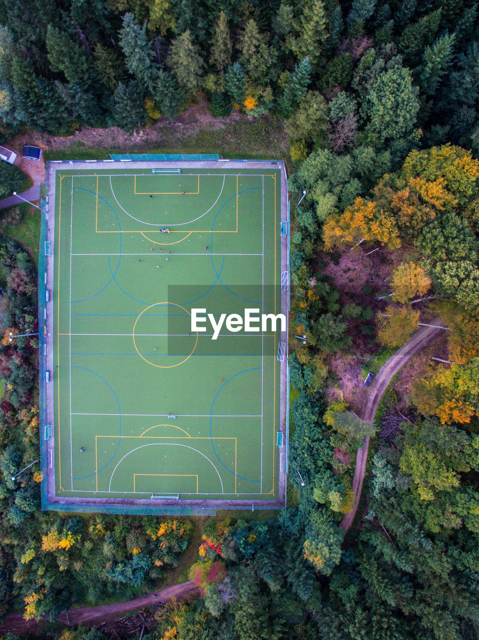 Aerial view of soccer field amidst trees during autumn