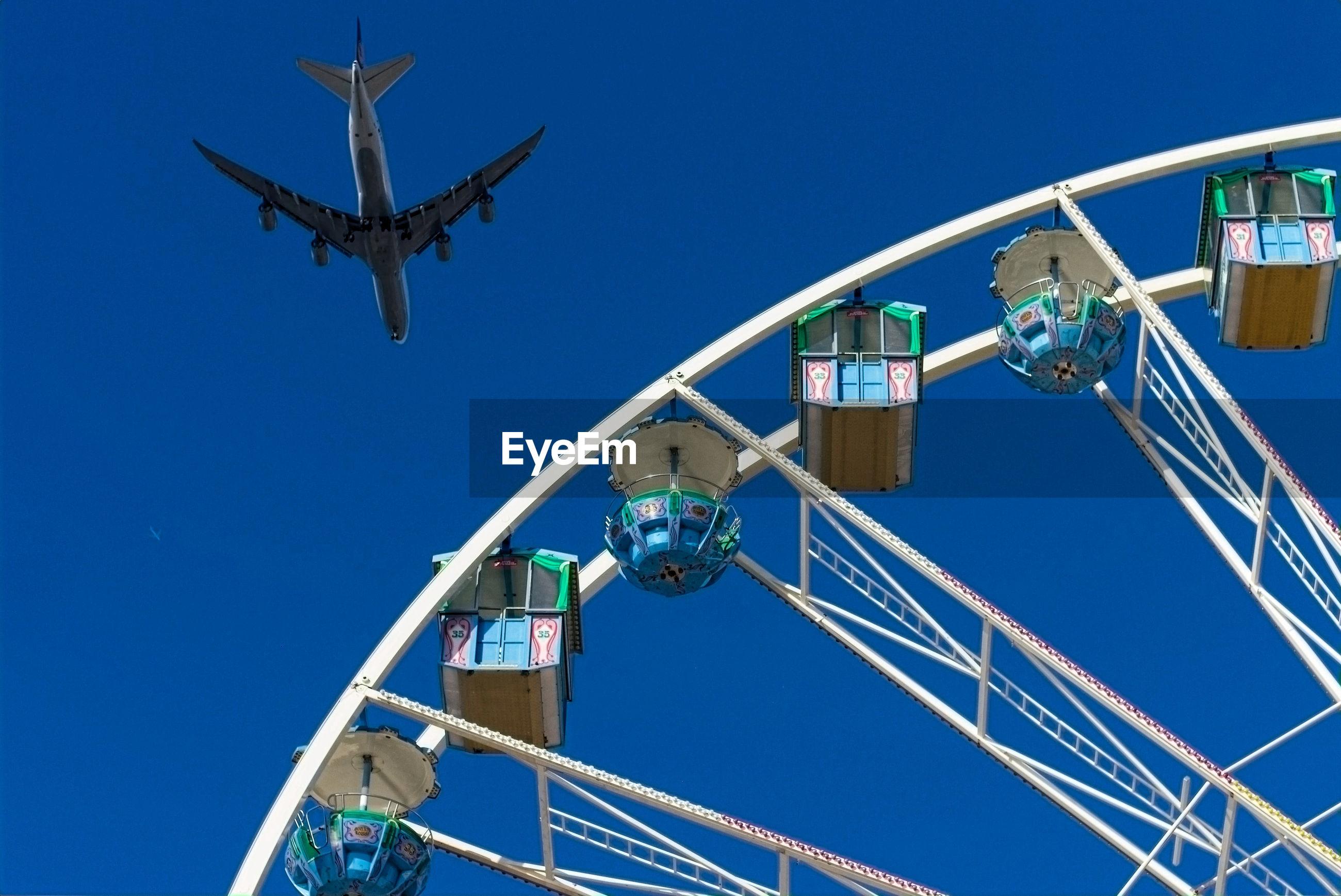 LOW ANGLE VIEW OF AMUSEMENT PARK RIDE AGAINST BLUE SKY