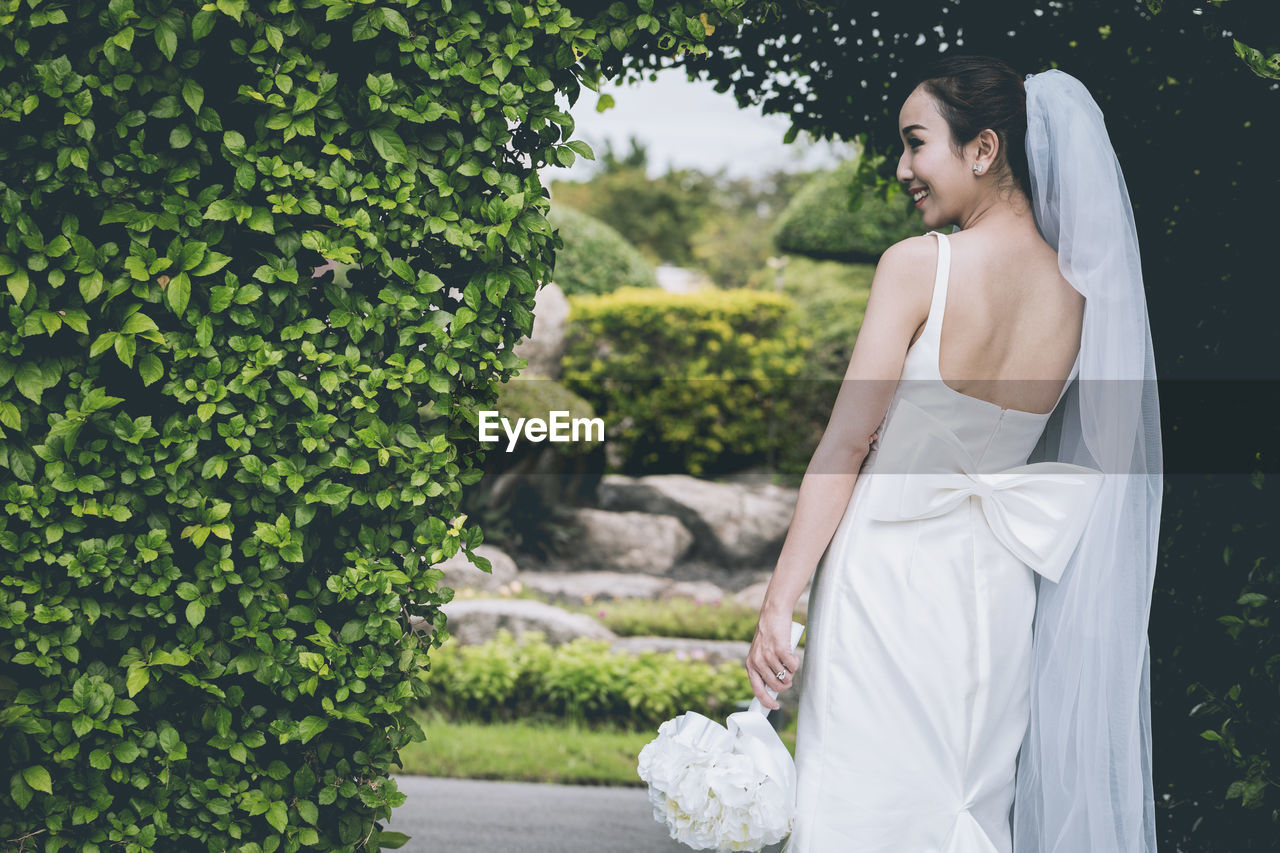 Rear view of bride standing in park