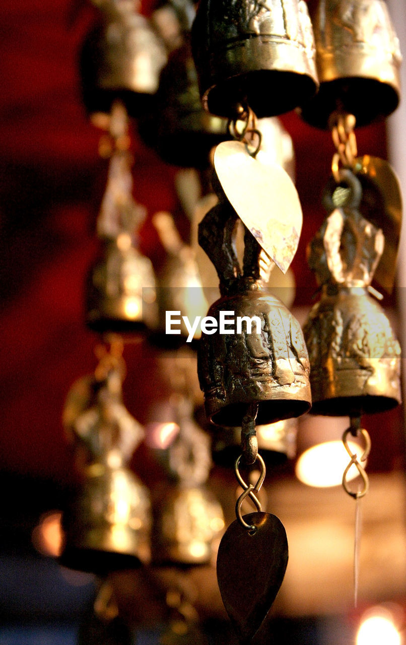 hanging, still life, focus on foreground, no people, lighting equipment, indoors, illuminated, gold colored, close-up, table, bell, day