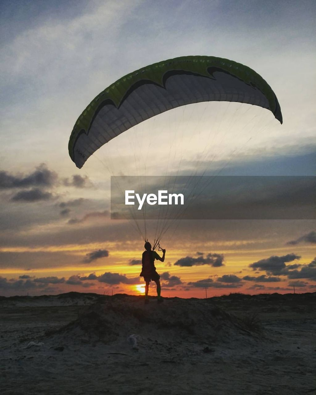 Rear view of man standing with parachute against orange sky