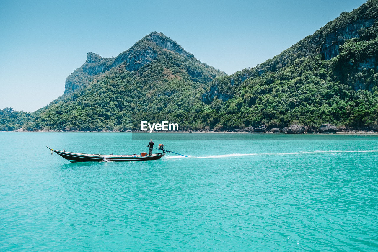 Man Sailing On Boat By Tree Mountains In Ko Samui
