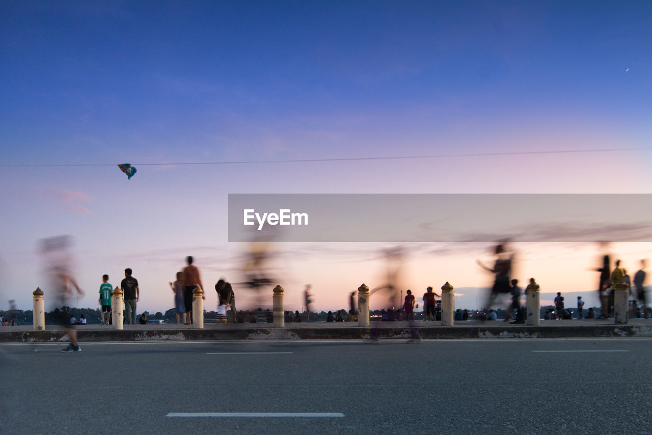 sky, sunset, city, nature, real people, building exterior, architecture, group of people, motion, lifestyles, leisure activity, men, outdoors, built structure, dusk, people, medium group of people, group, transportation, sport, cityscape