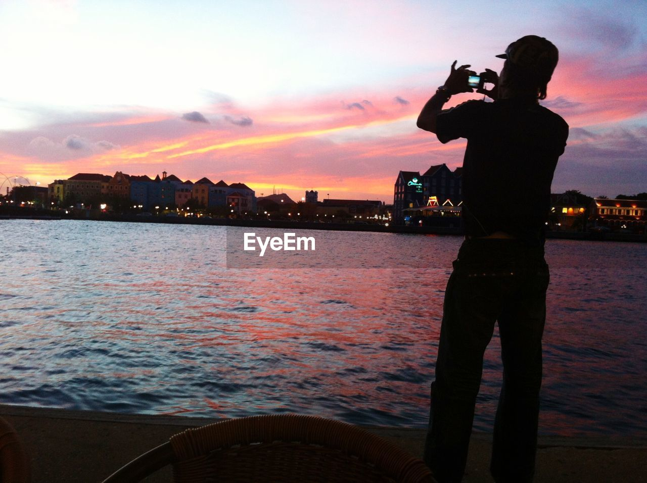 Rear view of silhouette man photographing at harbor in willemstad during sunset