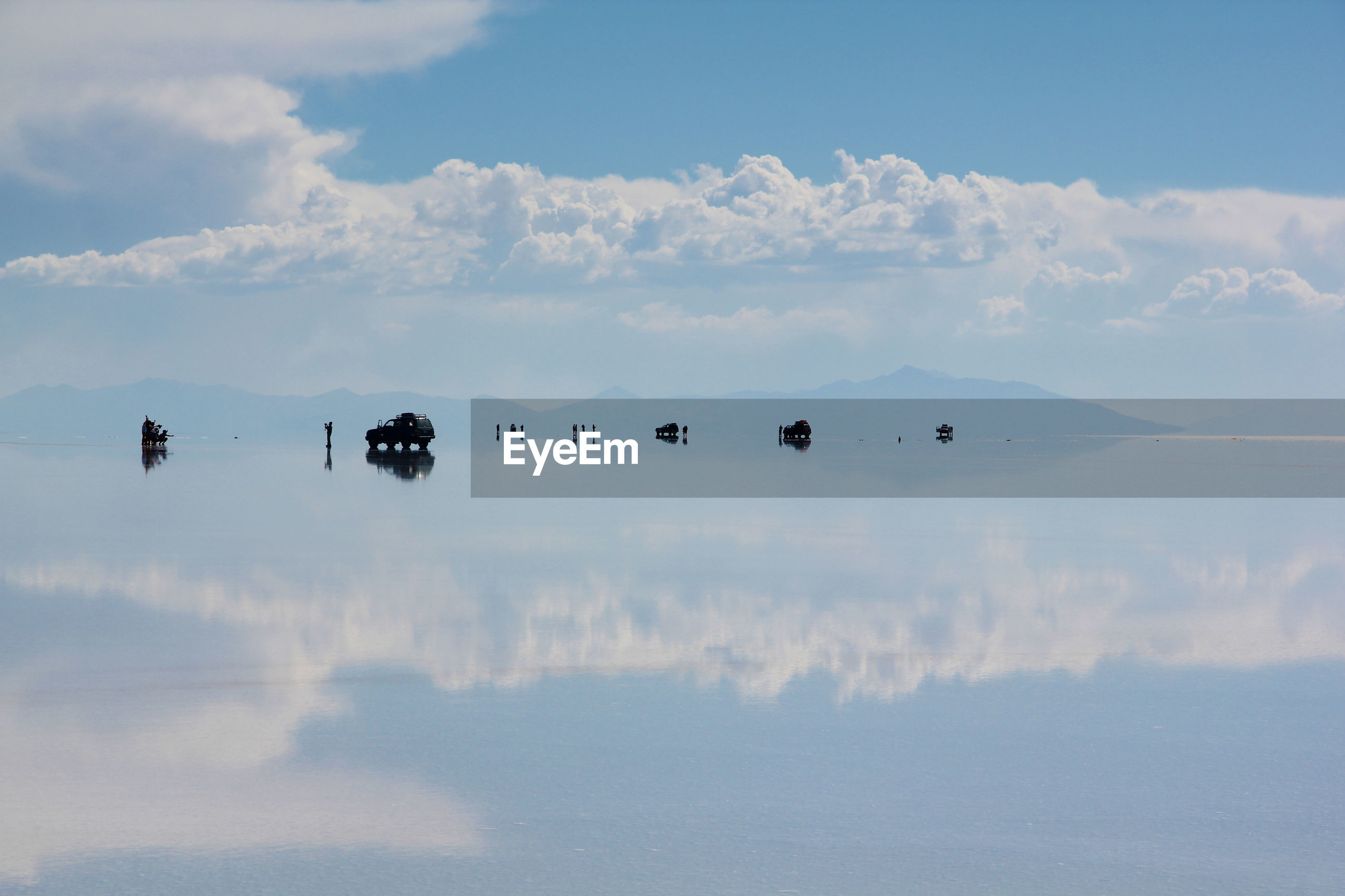Tourists and vehicles reflection in water at salar de uyuni against sky