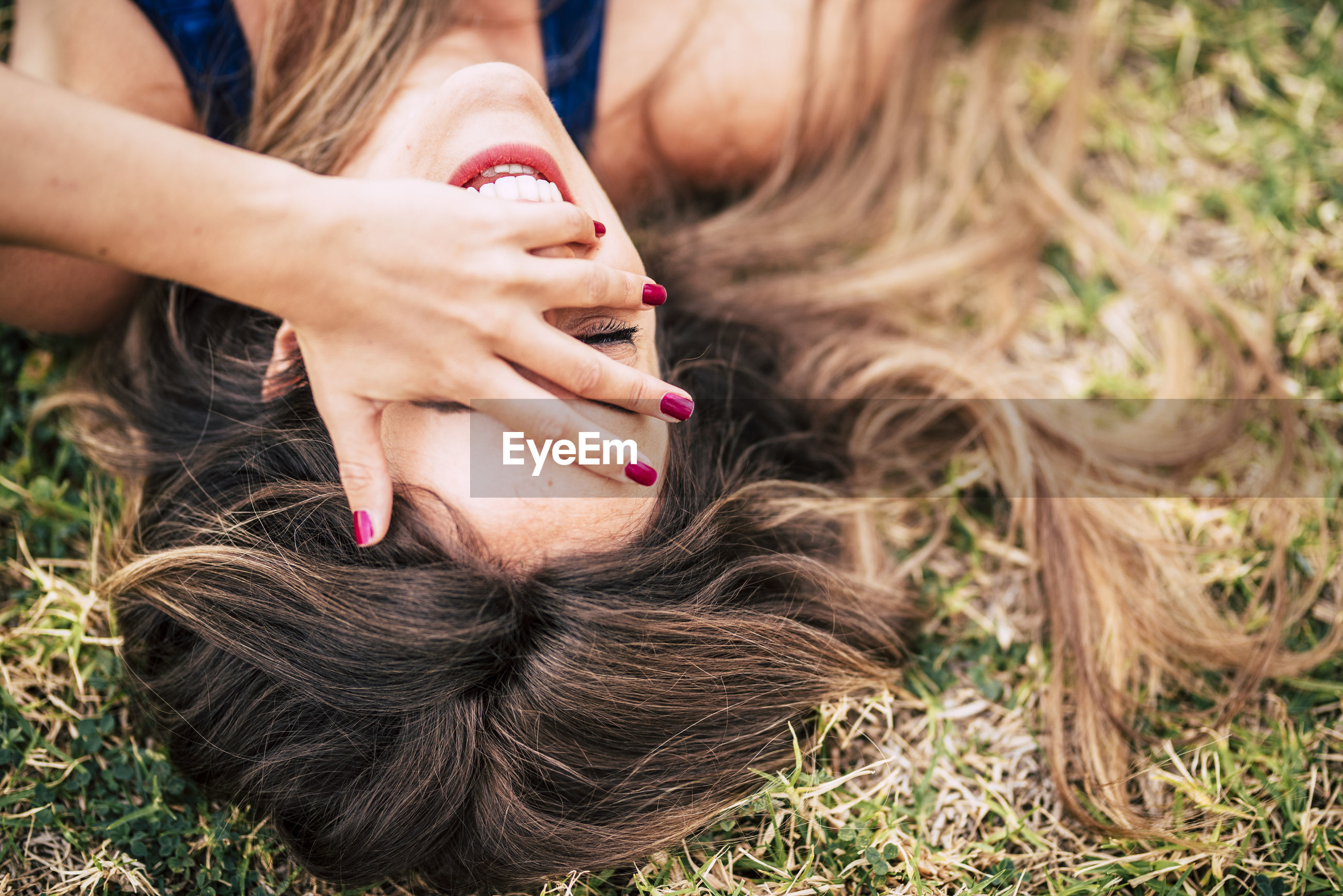 High angle view of smiling woman lying on grass