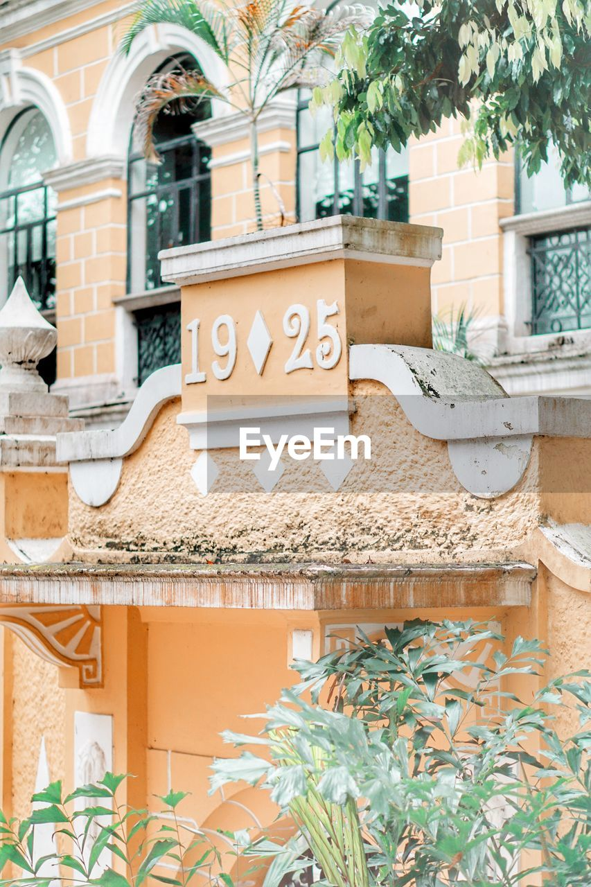 building exterior, architecture, built structure, text, plant, communication, day, western script, no people, building, nature, tree, outdoors, growth, sign, wall, low angle view, wall - building feature, potted plant, leaf