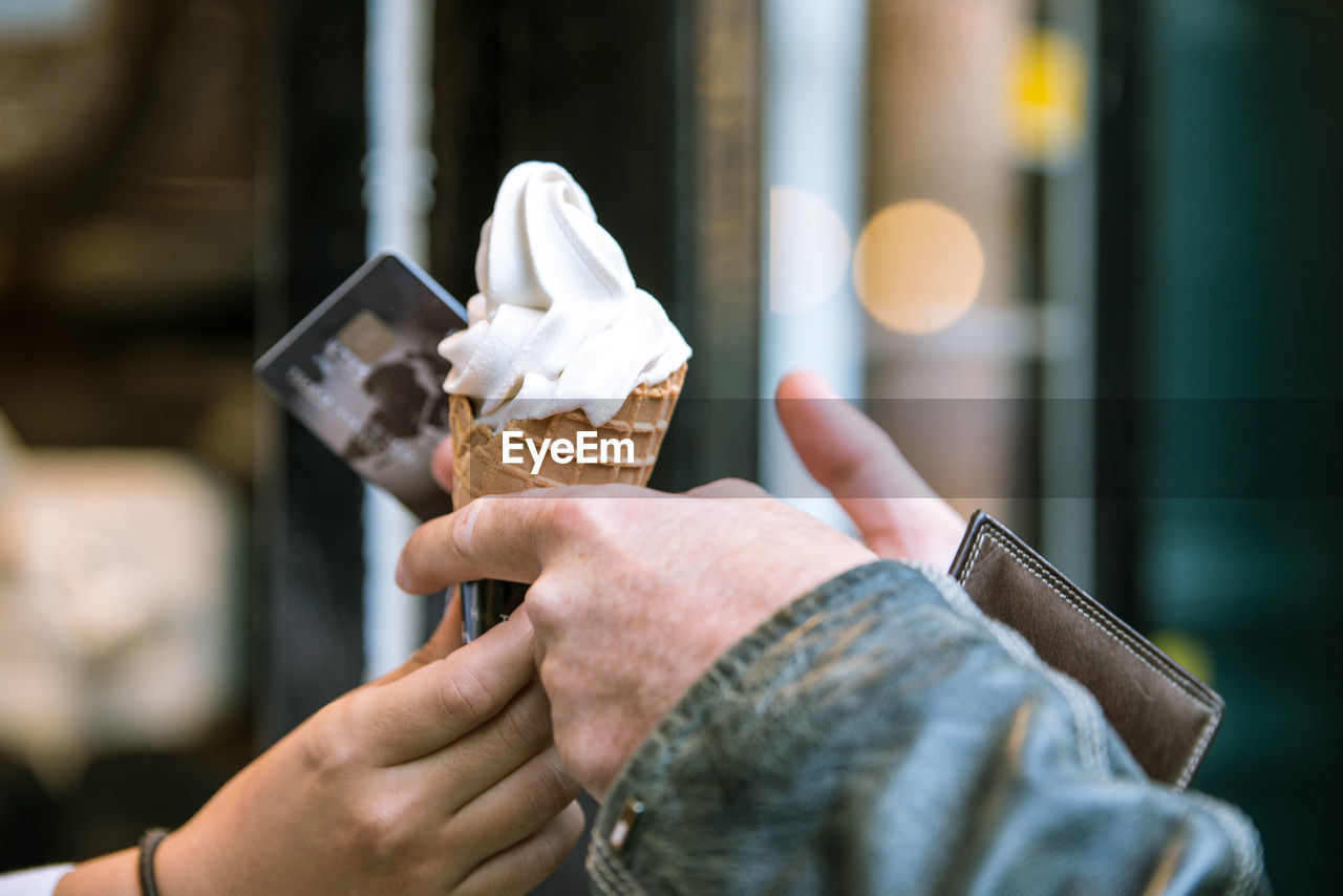 Close-Up Of Hands Holding Ice Cream