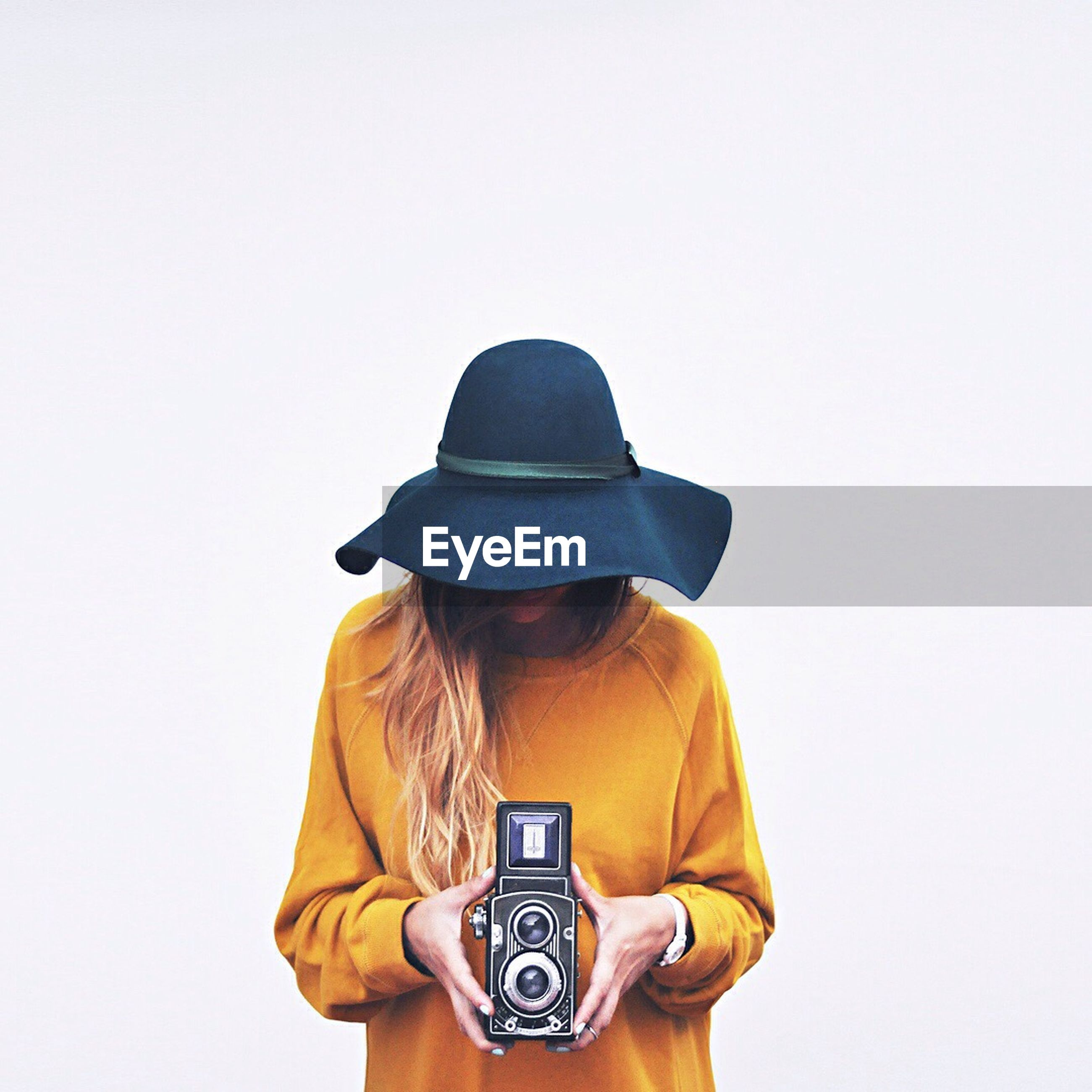 Woman holding camera against white background
