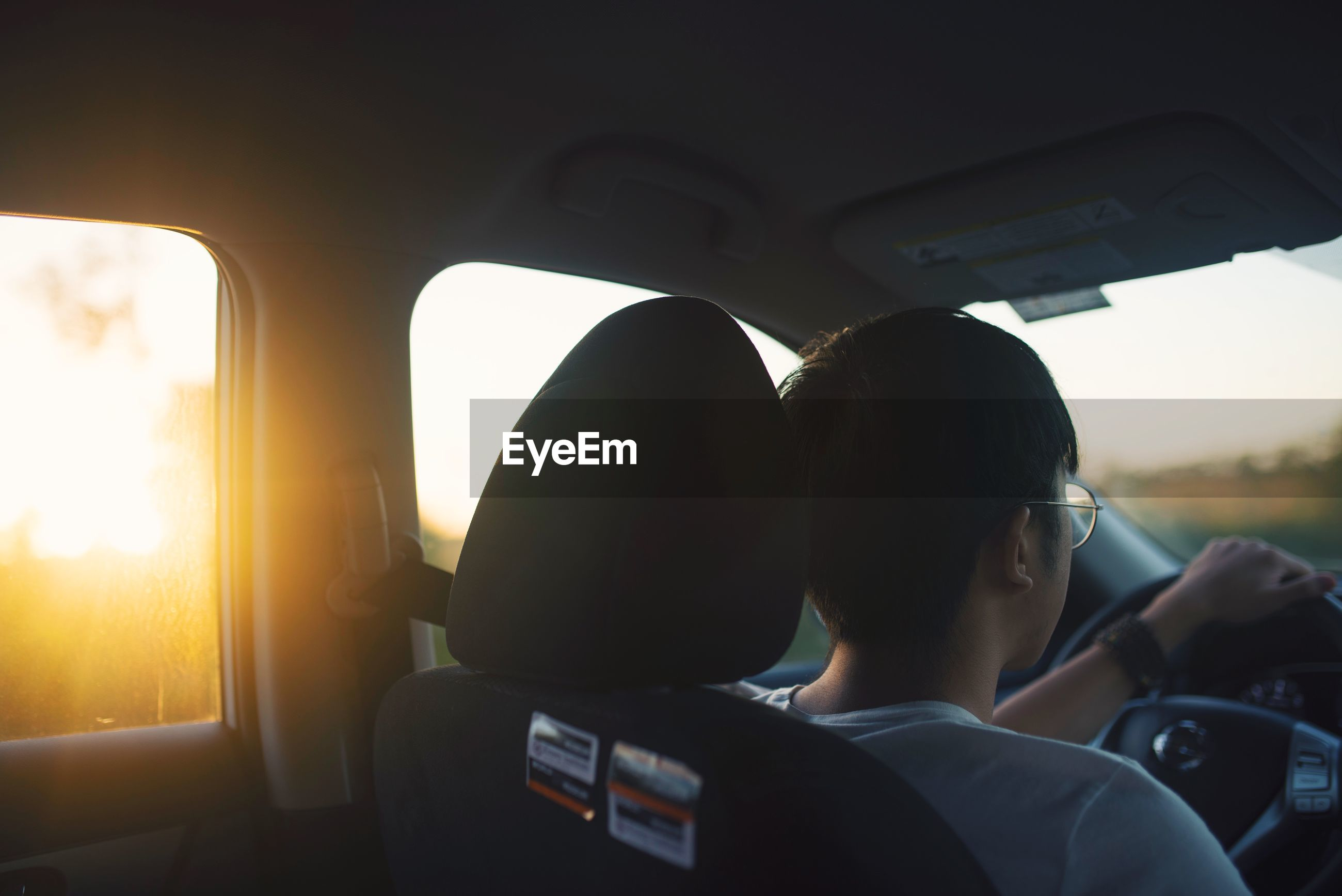 REAR VIEW OF PEOPLE SITTING IN CAR