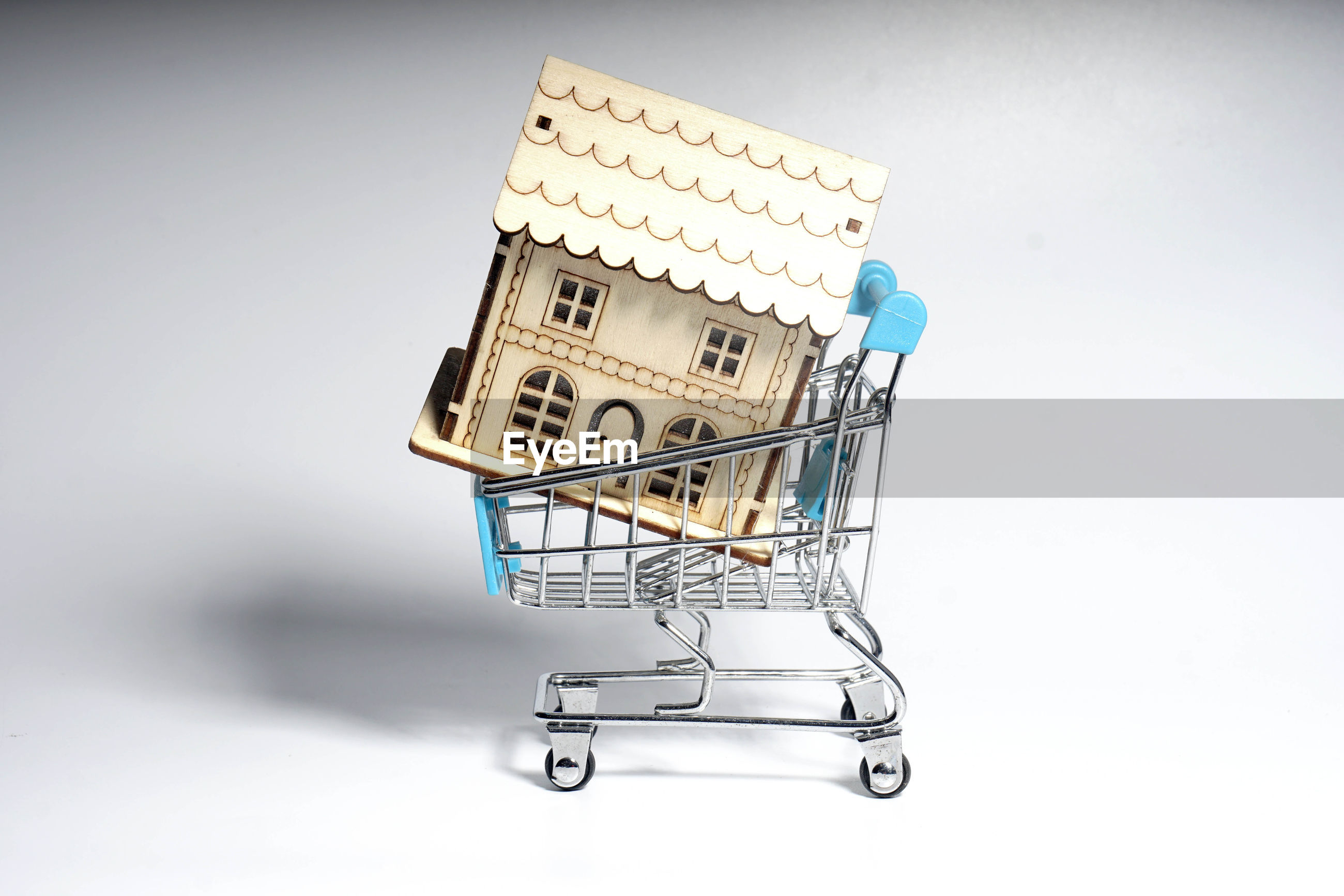 Close-up of model home in miniature shopping cart against white background