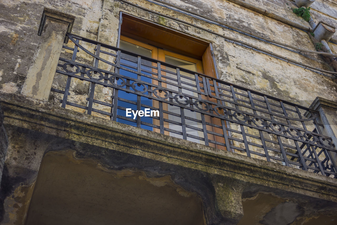 window, architecture, built structure, building, building exterior, low angle view, no people, old, day, abandoned, railing, wall - building feature, house, wall, outdoors, reflection, glass - material, weathered, residential district, damaged