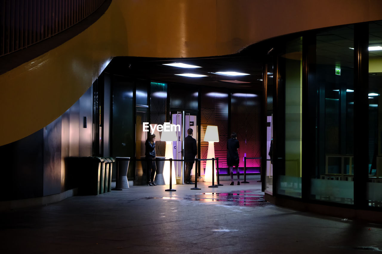 illuminated, architecture, real people, indoors, built structure, women, lifestyles, lighting equipment, standing, people, men, full length, the way forward, direction, adult, building, reflection, architectural column, walking, flooring, ceiling