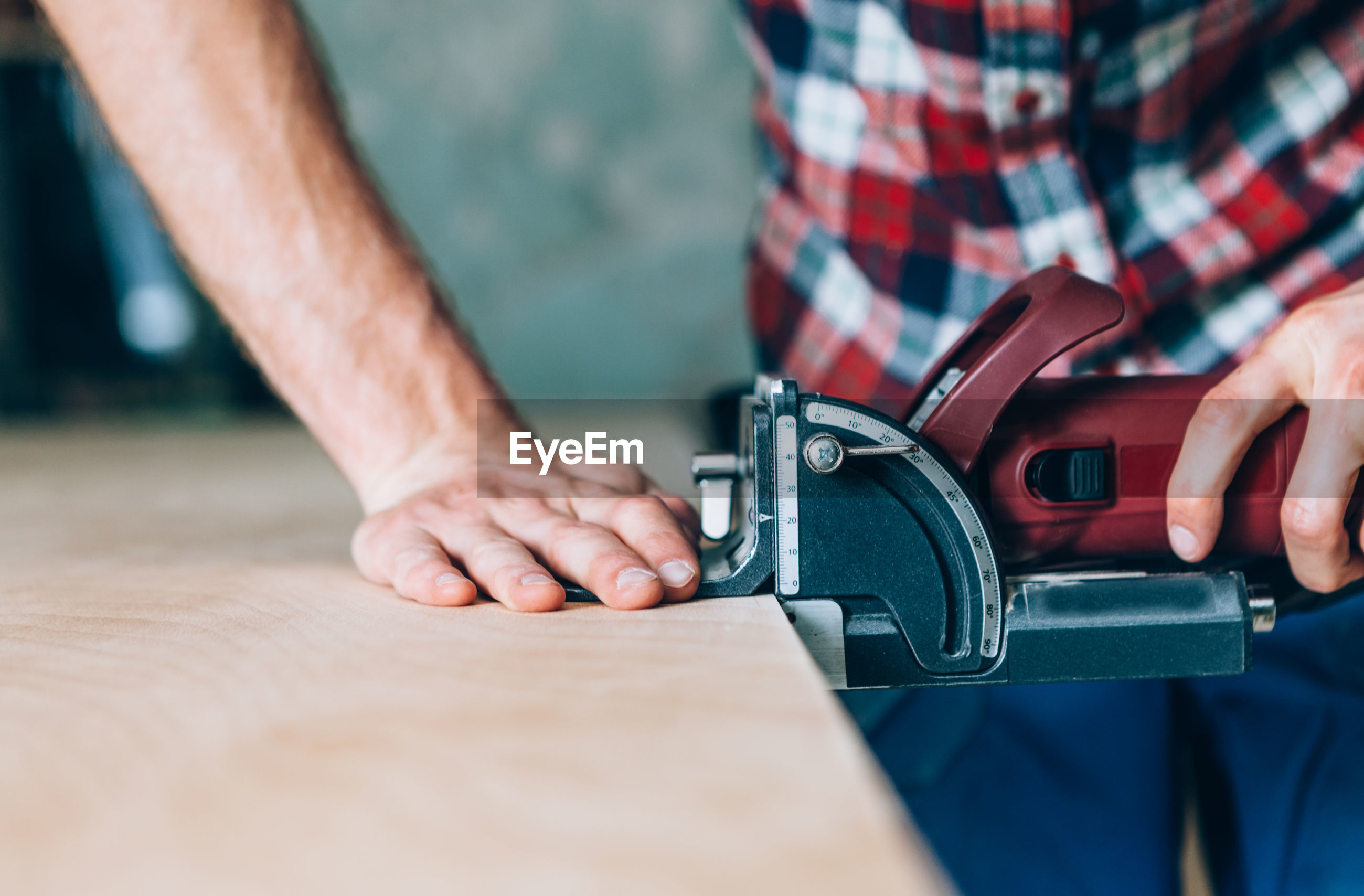 Midsection of carpenter using machinery while working in carpentry workshop