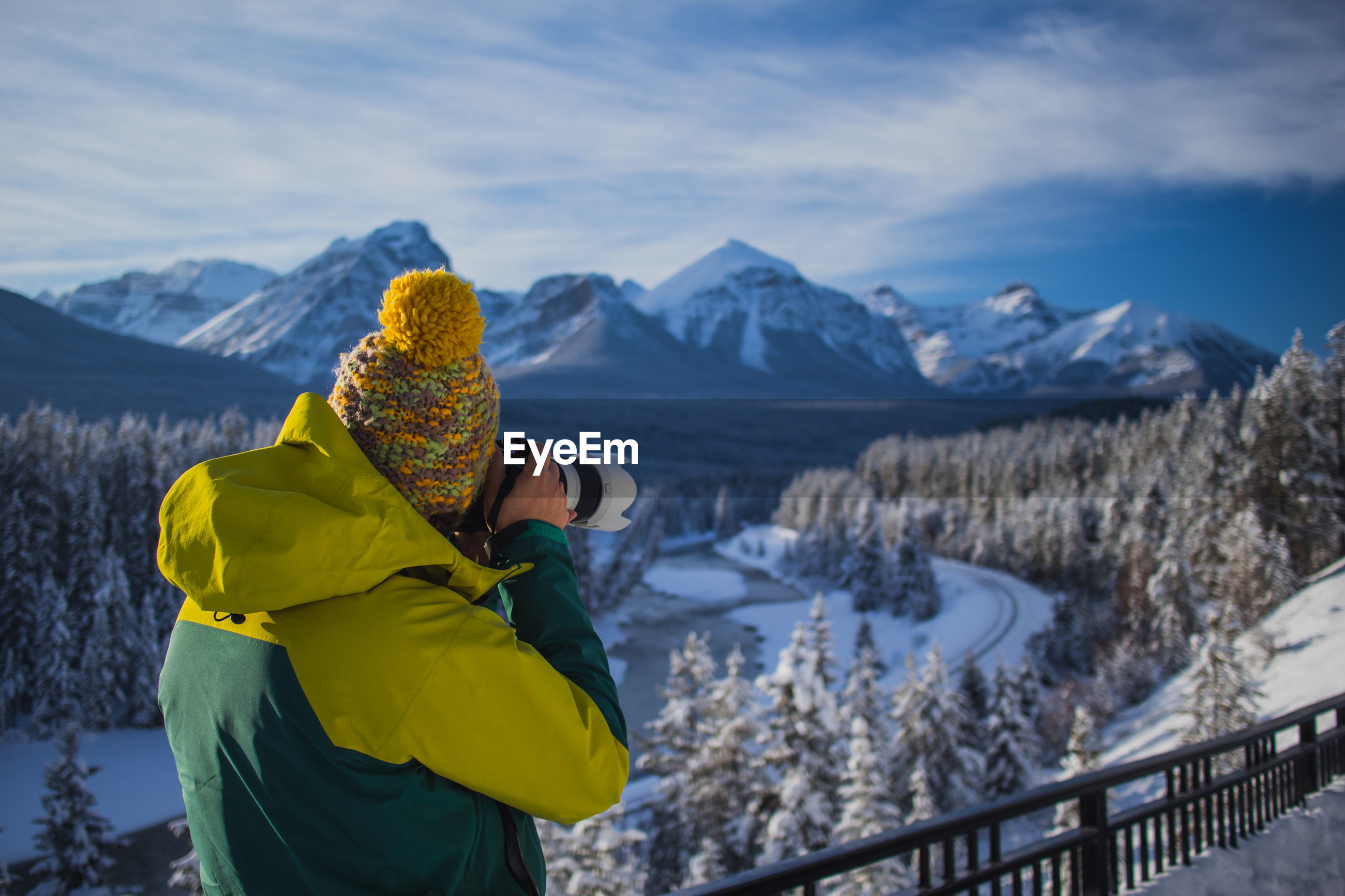 Man with camera standing against snow covered mountain in morning