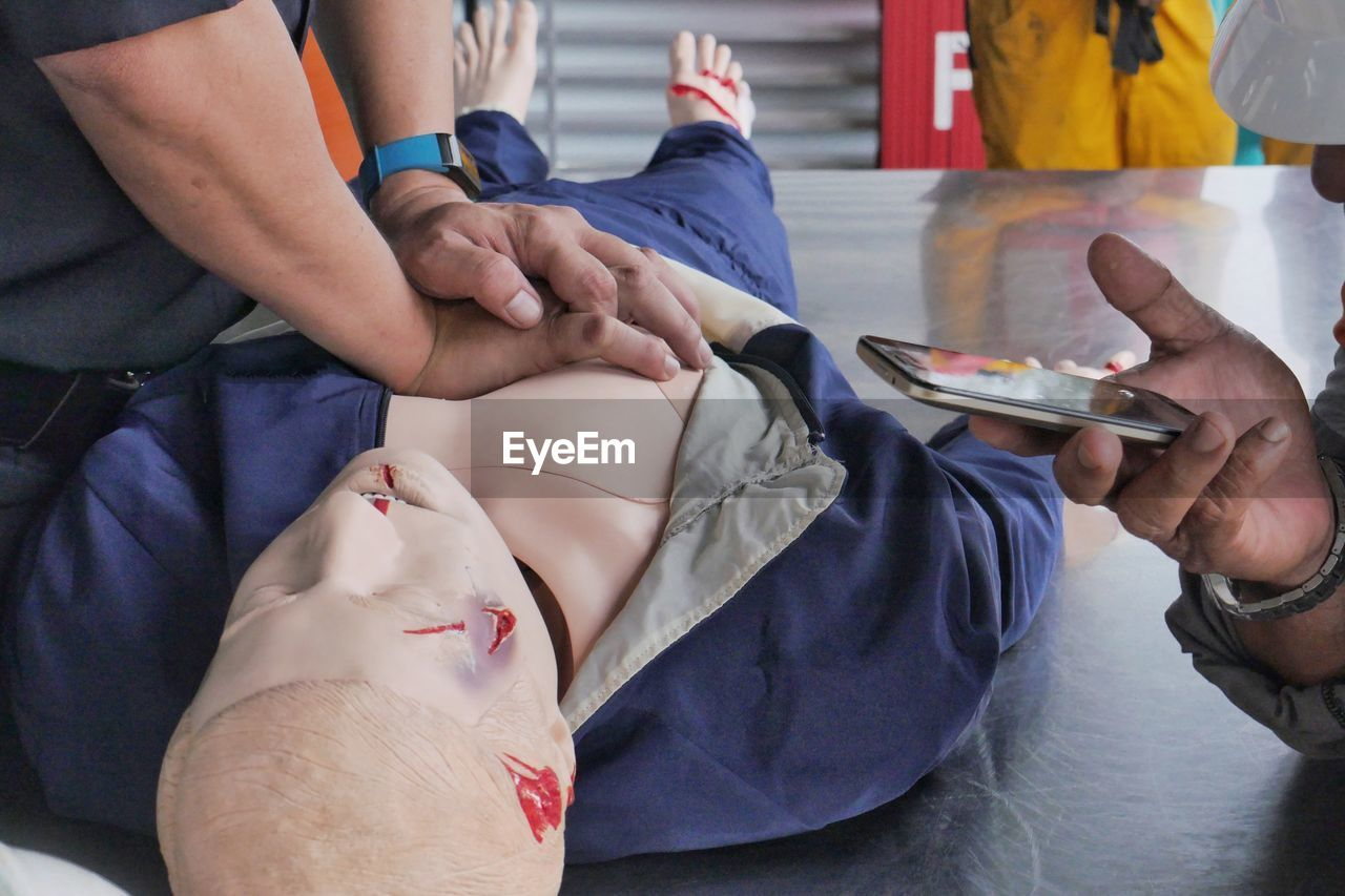 Close-up of instructor teaching paramedic while performing cpr on dummy