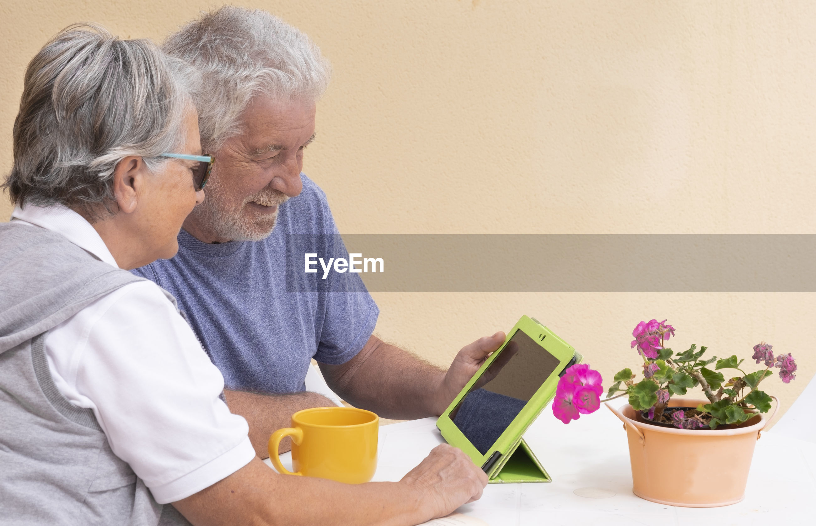 Senior couple using digital tablet at table