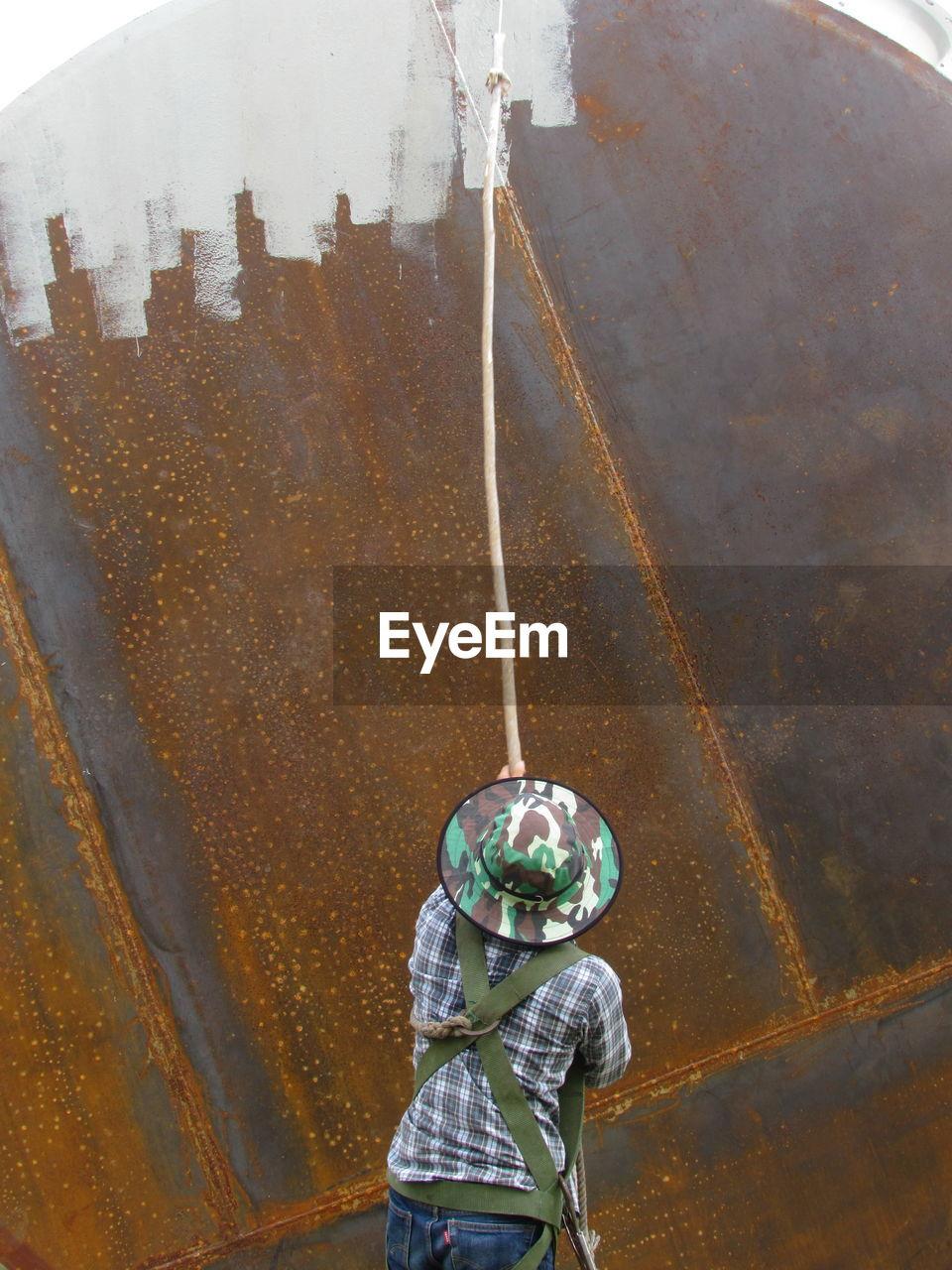 Rear view of man painting rusty metallic wall