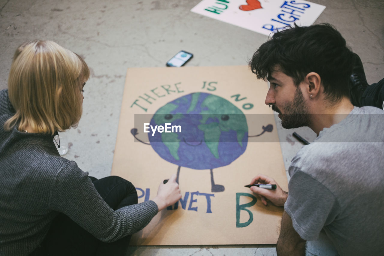 HIGH ANGLE VIEW OF PEOPLE HOLDING TEXT ON FLOOR