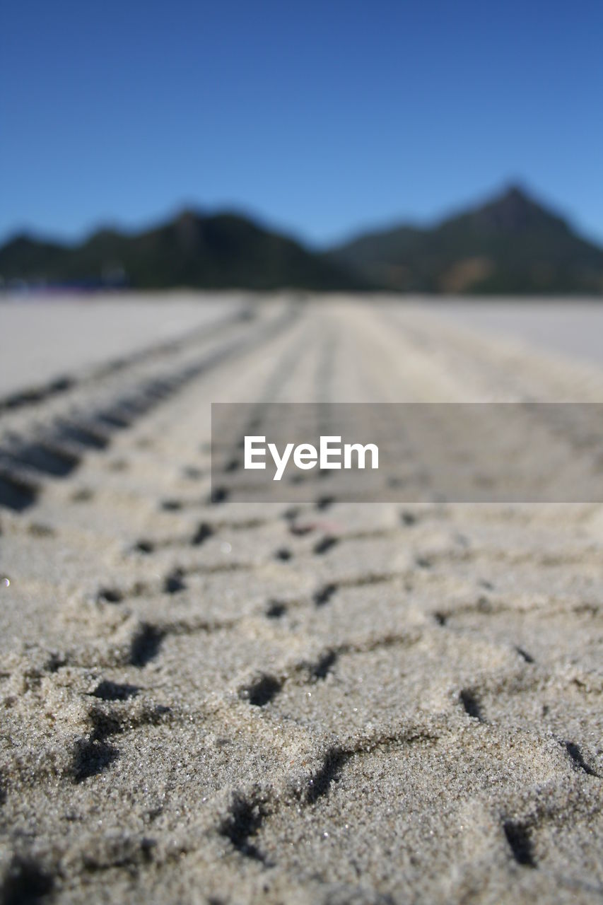 sand, beach, nature, outdoors, day, surface level, no people, tire track, sunlight, selective focus, close-up, tranquil scene, tranquility, focus on foreground, beauty in nature, scenics, sky