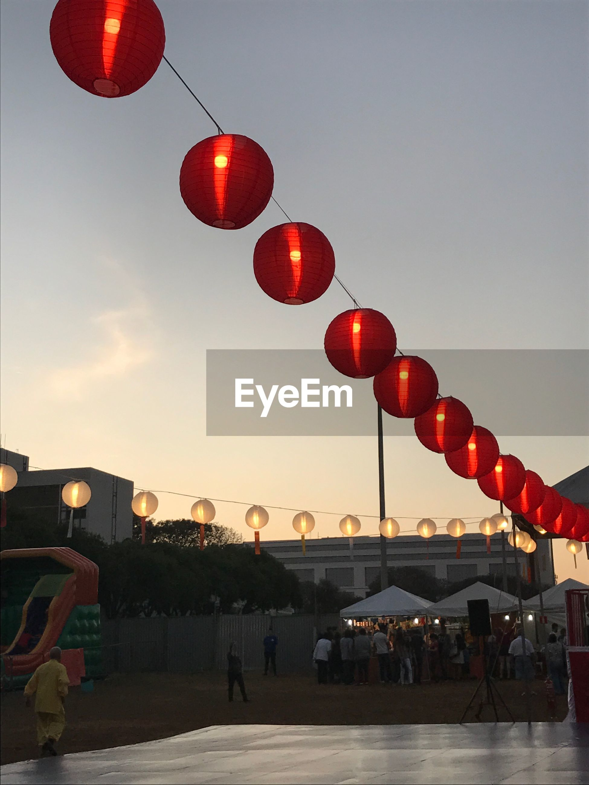sky, built structure, lighting equipment, architecture, building exterior, illuminated, red, incidental people, nature, lantern, hanging, transportation, low angle view, outdoors, chinese lantern, city, dusk, in a row, street, light, chinese lantern festival