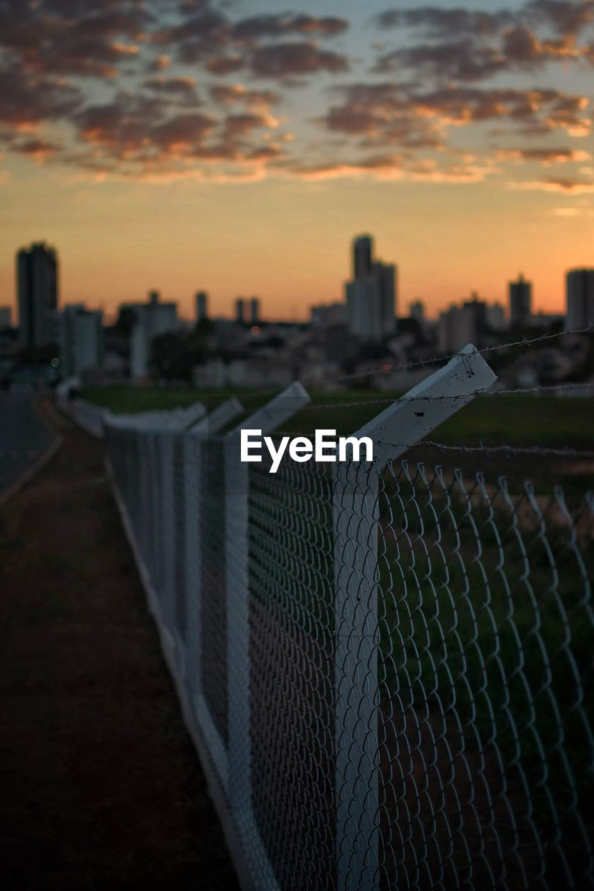 sky, sunset, architecture, city, built structure, building exterior, security, cityscape, cloud - sky, nature, building, safety, no people, protection, skyscraper, fence, urban skyline, boundary, office building exterior, orange color, outdoors