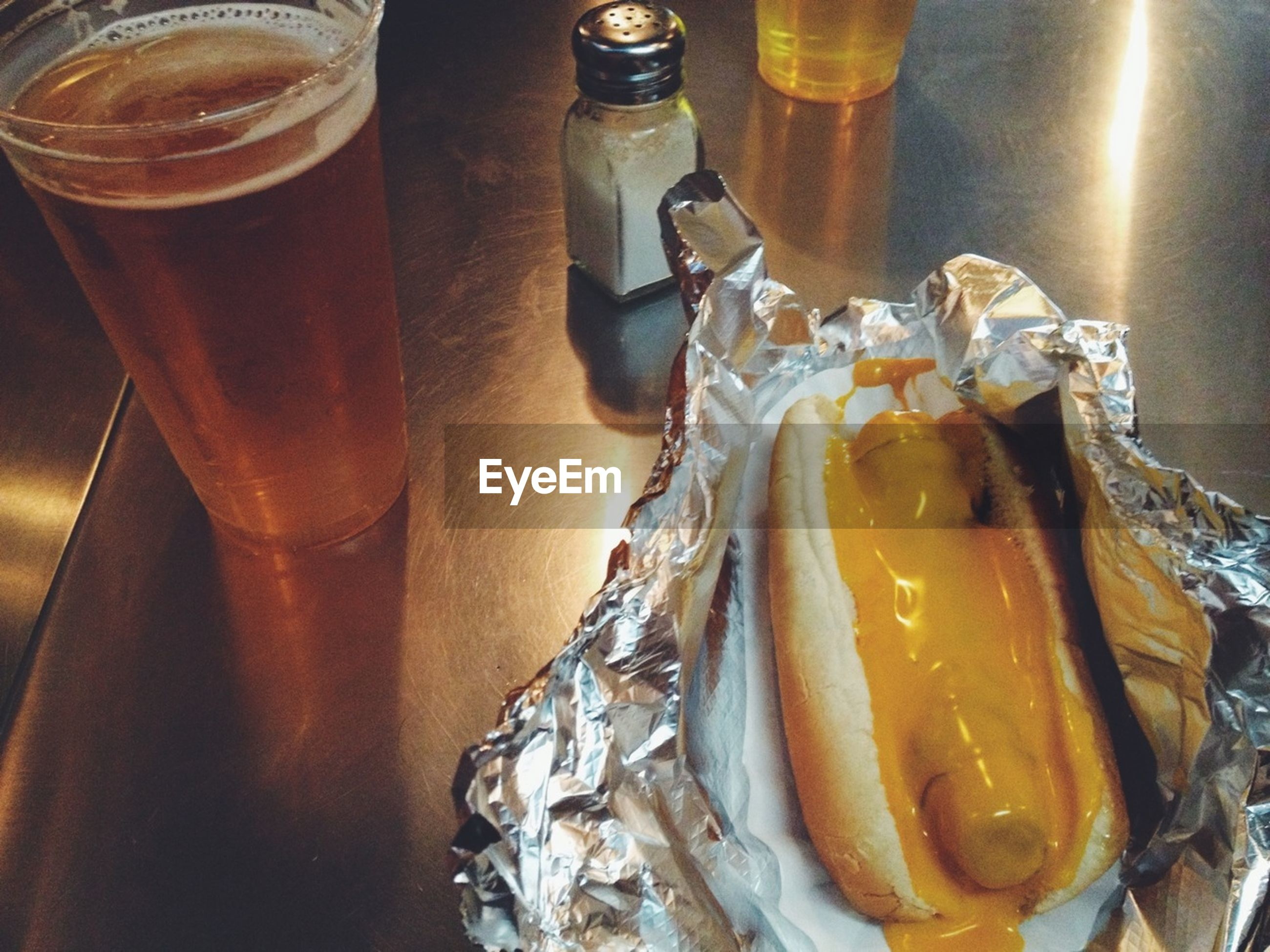 Close-up of hot dog and beer glass on table