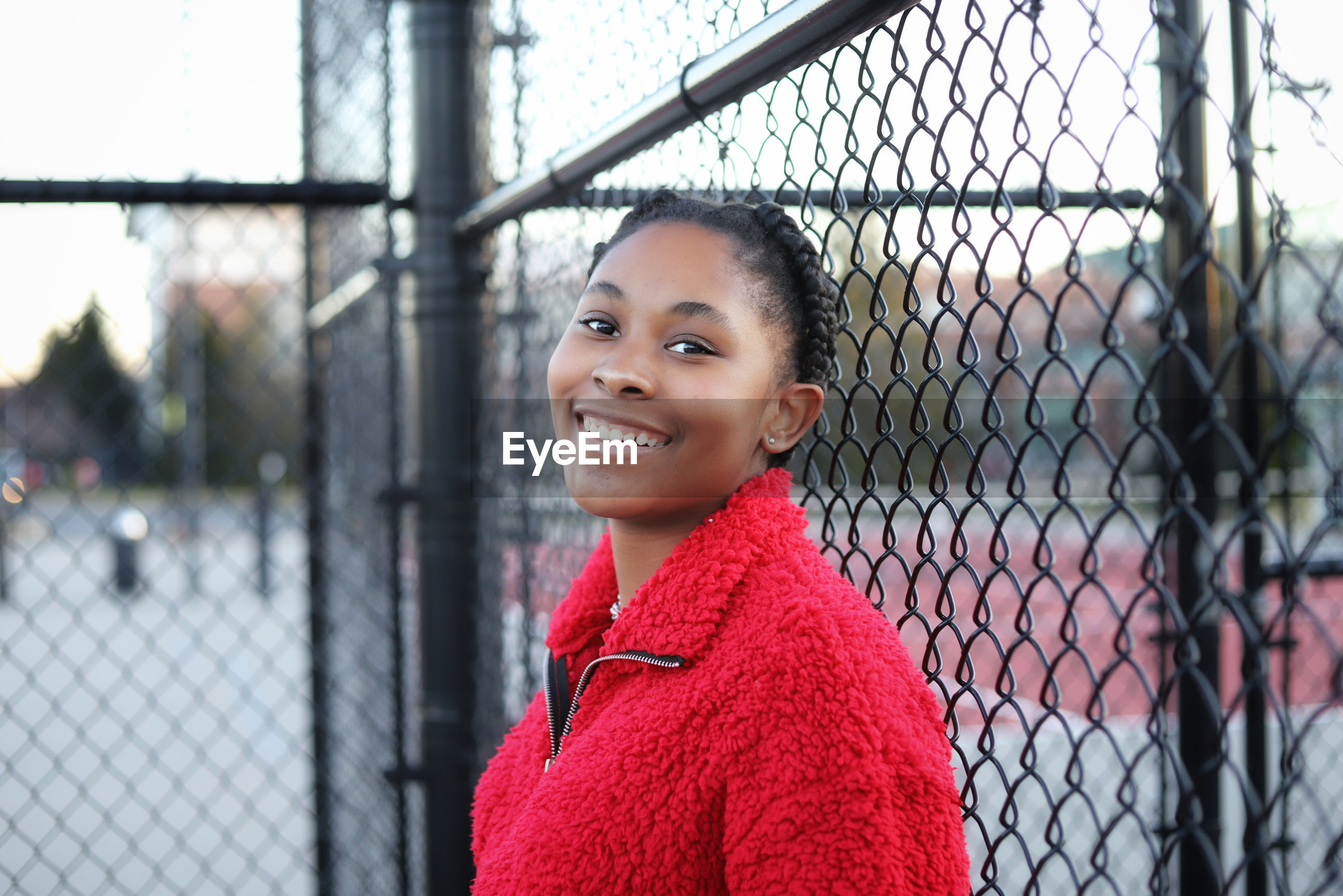 Portrait of smiling girl standing against chainlink fence