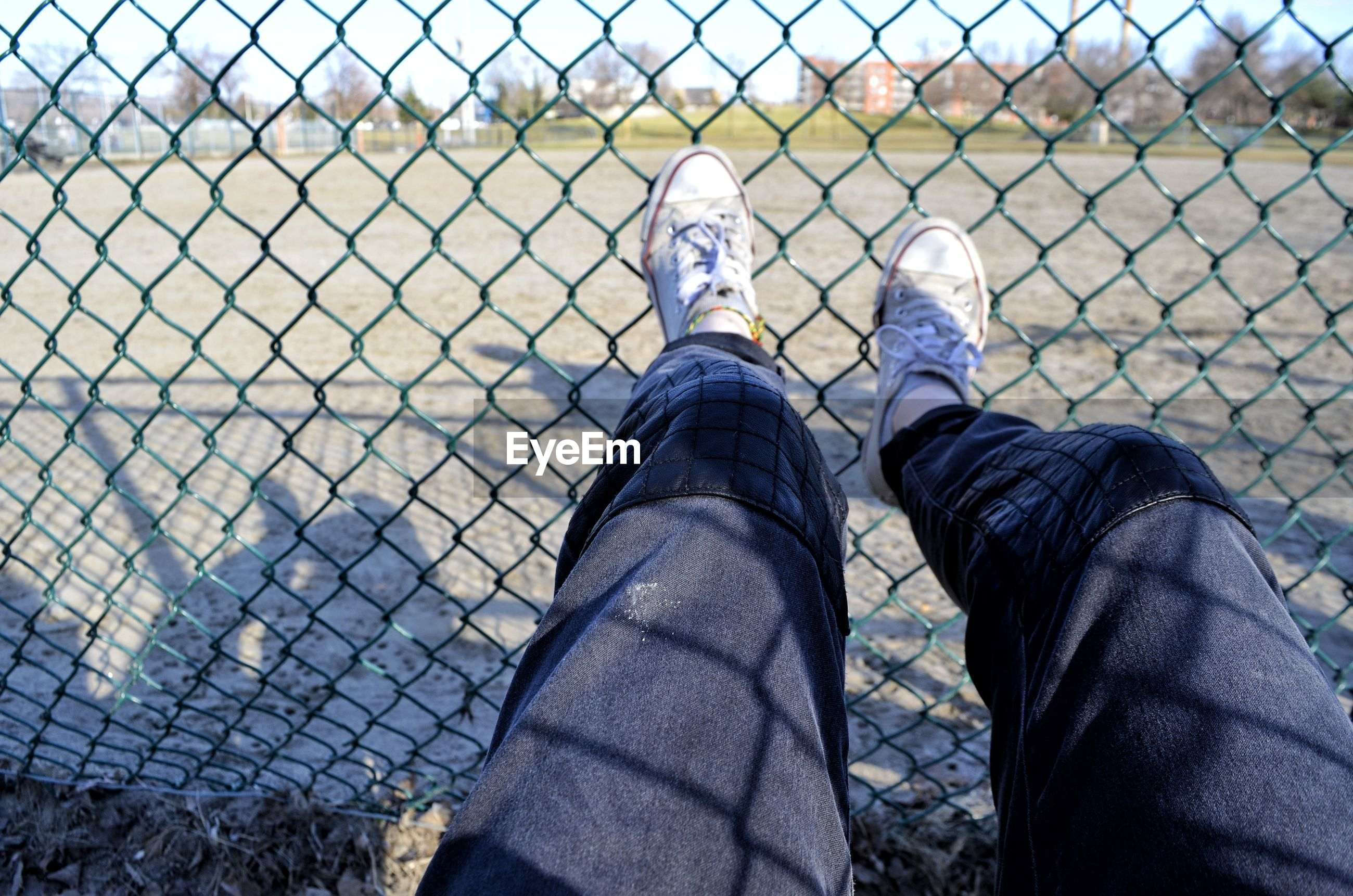 Low section of man on chainlink fence