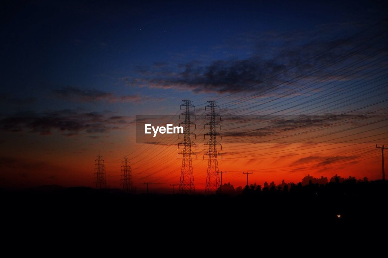 View Of Electricity Pylons During Sunset