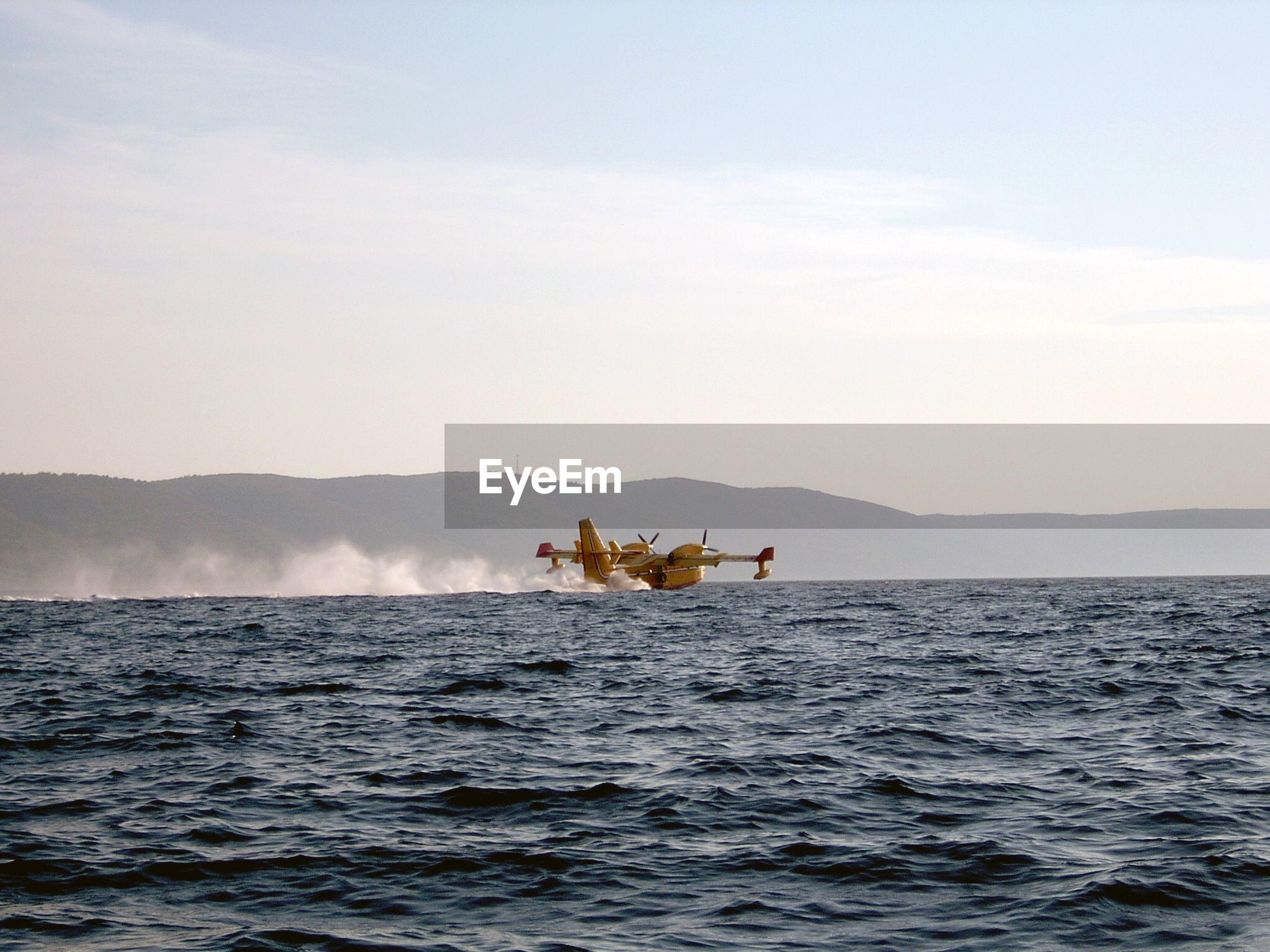 View of airplane landing in sea against sky