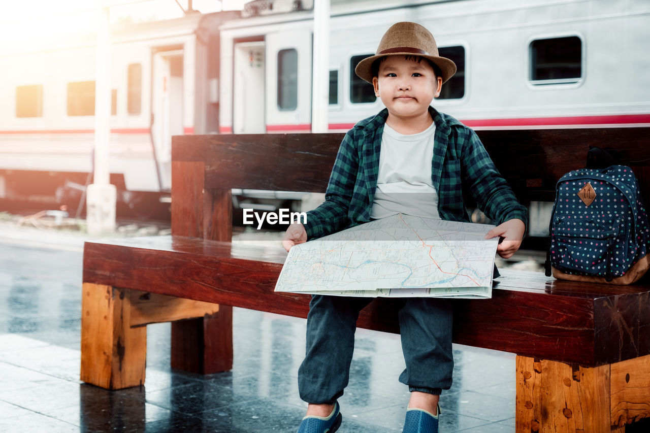 real people, one person, looking at camera, hat, males, clothing, front view, childhood, portrait, child, men, casual clothing, boys, leisure activity, day, standing, mode of transportation, lifestyles, innocence, uniform
