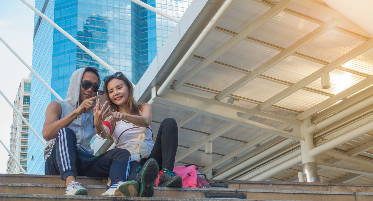 Low angle view of friends sitting on steps against building