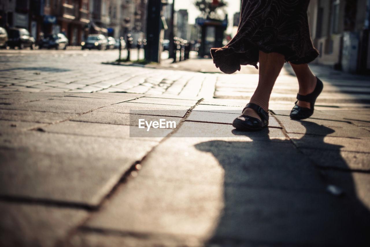 Low Section View Of Woman Walking On Sidewalk