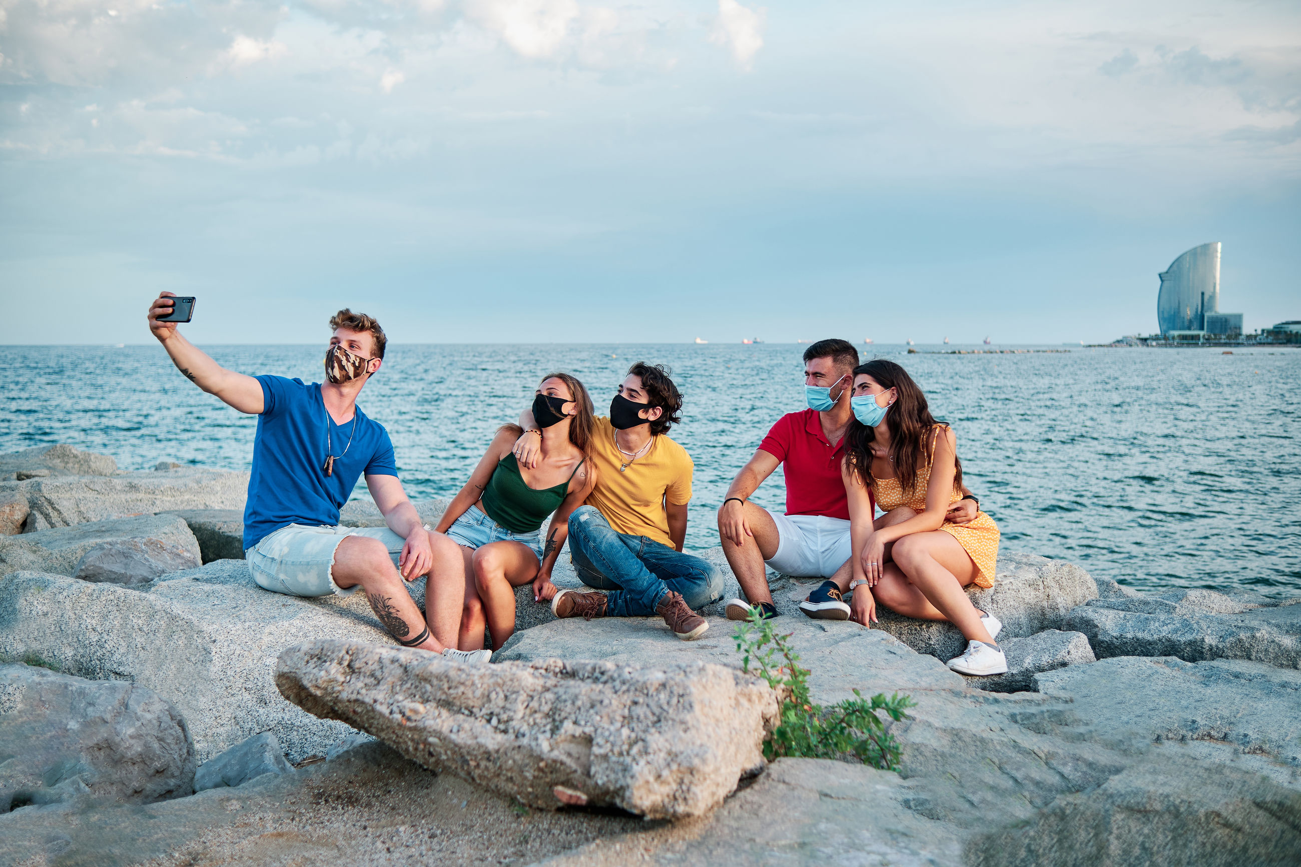 PEOPLE SITTING ON ROCK AGAINST SEA