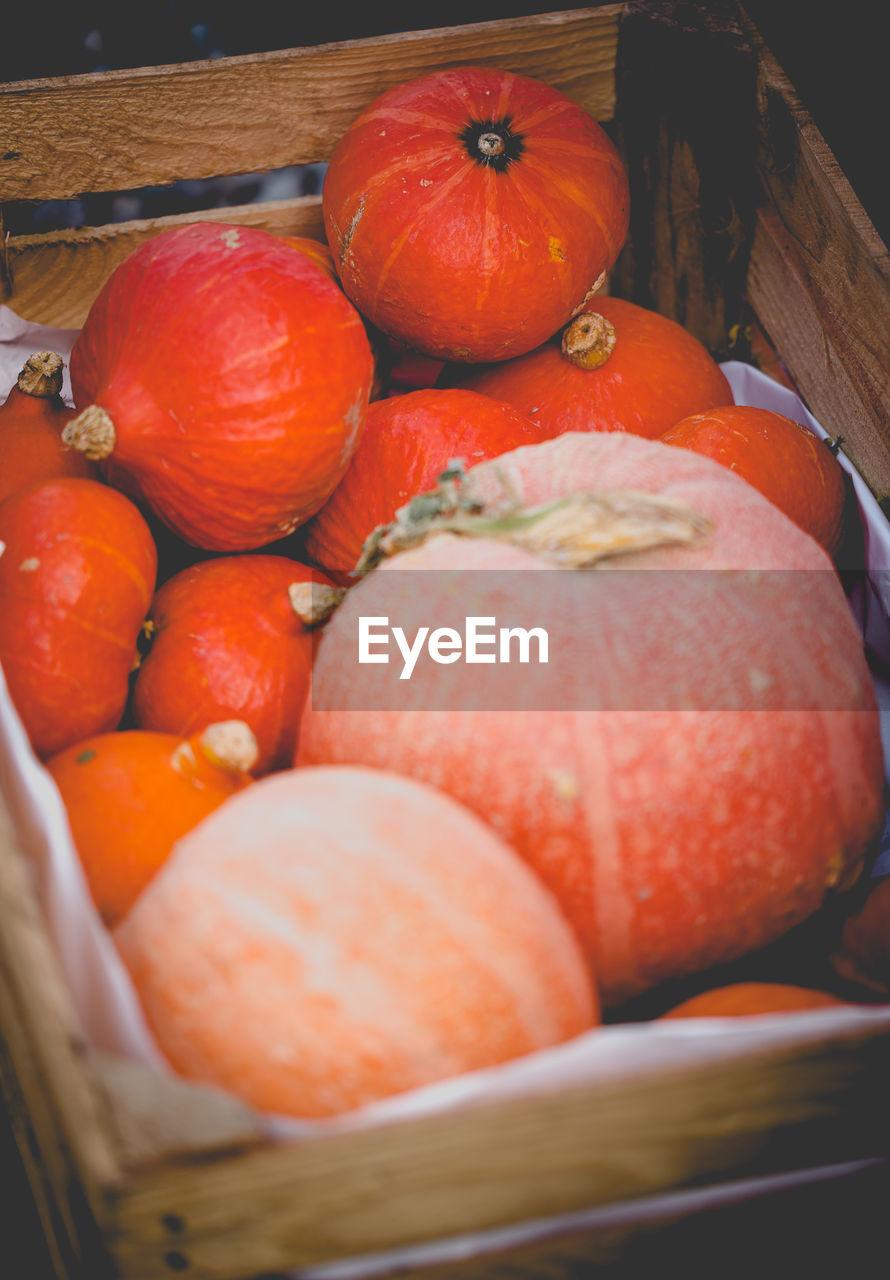 Close-up of pumpkins in basket for sale at market