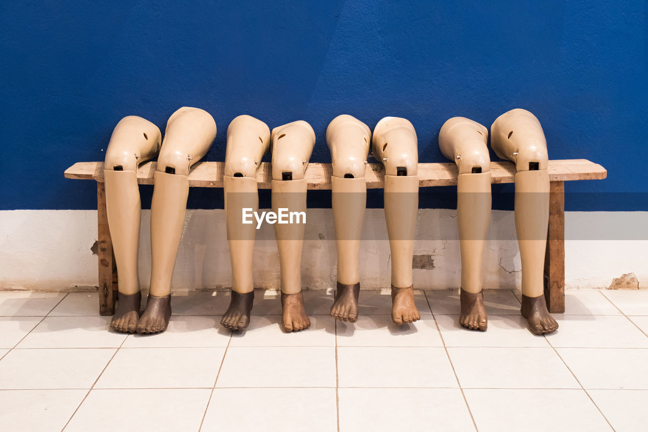 Close-up of mannequin on tiled floor by blue wall
