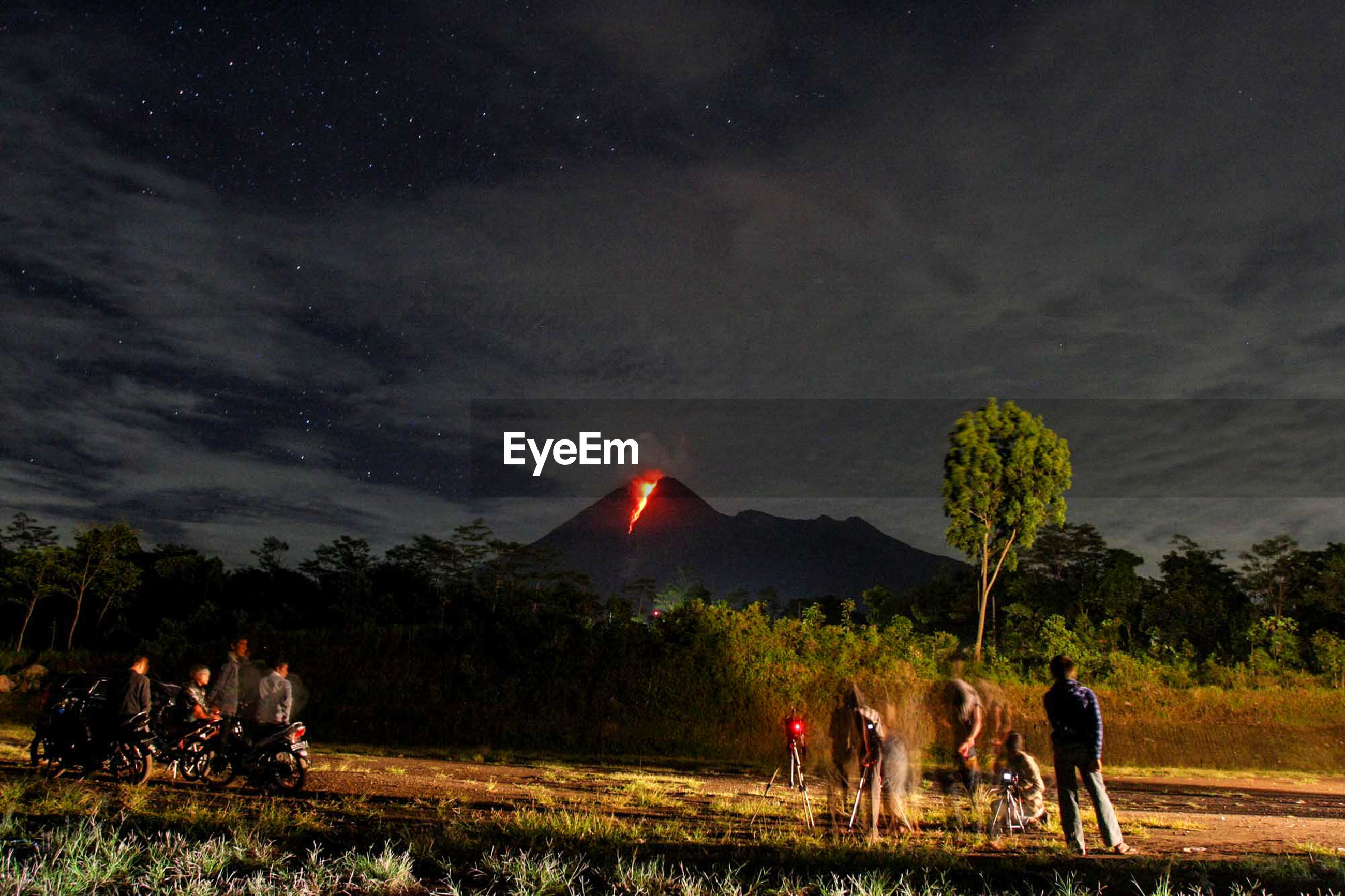 People watching mount merapi volcano eruption against sky at night
