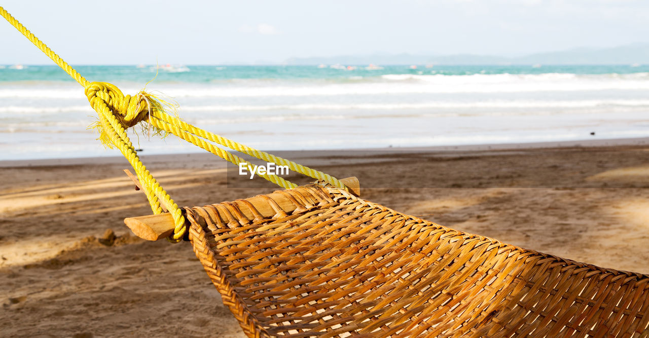 beach, sea, land, sand, water, sky, rope, day, nature, no people, focus on foreground, beauty in nature, wood - material, horizon over water, tranquility, tranquil scene, close-up, horizon, outdoors
